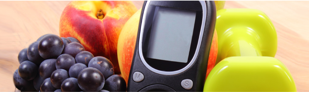 blood glucose meter beside fruit and a dumbbell